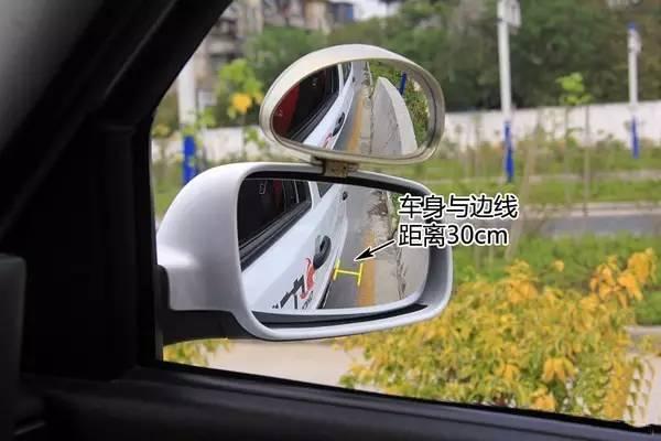 4、继续离合半联动控制车速,慢速靠近停车点,当左后视镜下沿与第二条粗黄线齐平时,先踩脚刹,后踩离合,将车停稳,关右转向灯。还有一种确定停车位置的方法,那就是看右边雨刮器上的凸起点,与停车标志牌的杆,还有眼睛成三点一线时,就可以踩离合踩刹车停车了。将车停稳之后,等待语音提示。(车内语音提示:定点准确)